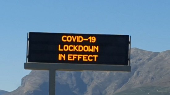 """A picture of an electronic roadsign, located in the Western Cape of South Africa, reading """"COVID-19 lockdown in effect""""."""