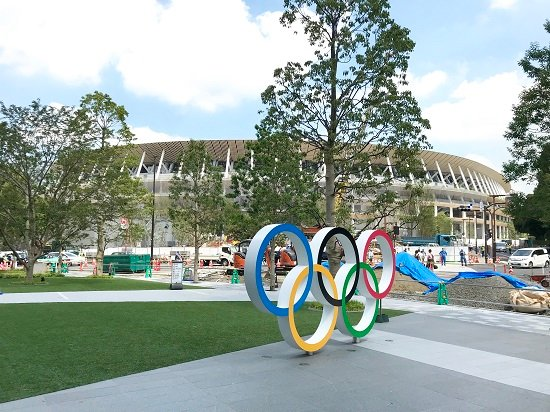 A picture of the Japan National Stadium in Tokyo, with a statue of the Olympic logo in the foreground.