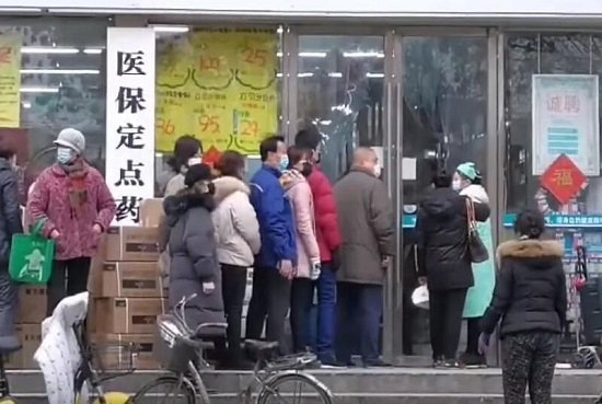 A picture of people lining up outside a drugstore in Wuhan, China, many of them wearing protective face masks.