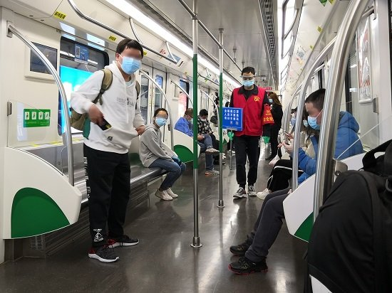 A picture of the interior of a Wuhan Metro train. Various passengers can be seen wearing protective face masks.